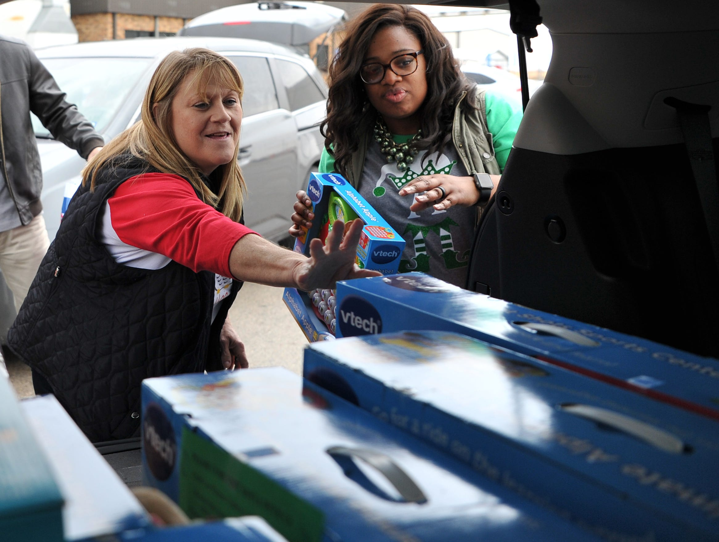 Child Care Partners employees Kelly Davis, left, and Anndrea Harris help load donated toys from Alcoa employees Thursday afternoon.