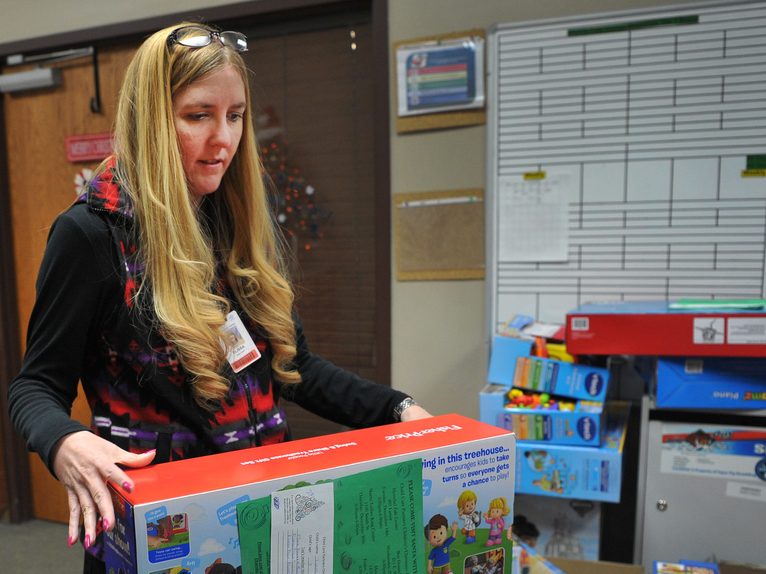 Alcoa Human Resource Specialist, Elissa Depew helps sort toys donated by Alcoa employees to Wichita Falls area Child Care Partners children Thursday afternoon.