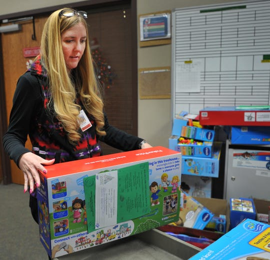 Acronic Human Resource Specialist, Elissa Depew helps sort toys donated by Acronic employees to Wichita Falls area Child Care Partners children Thursday afternoon.