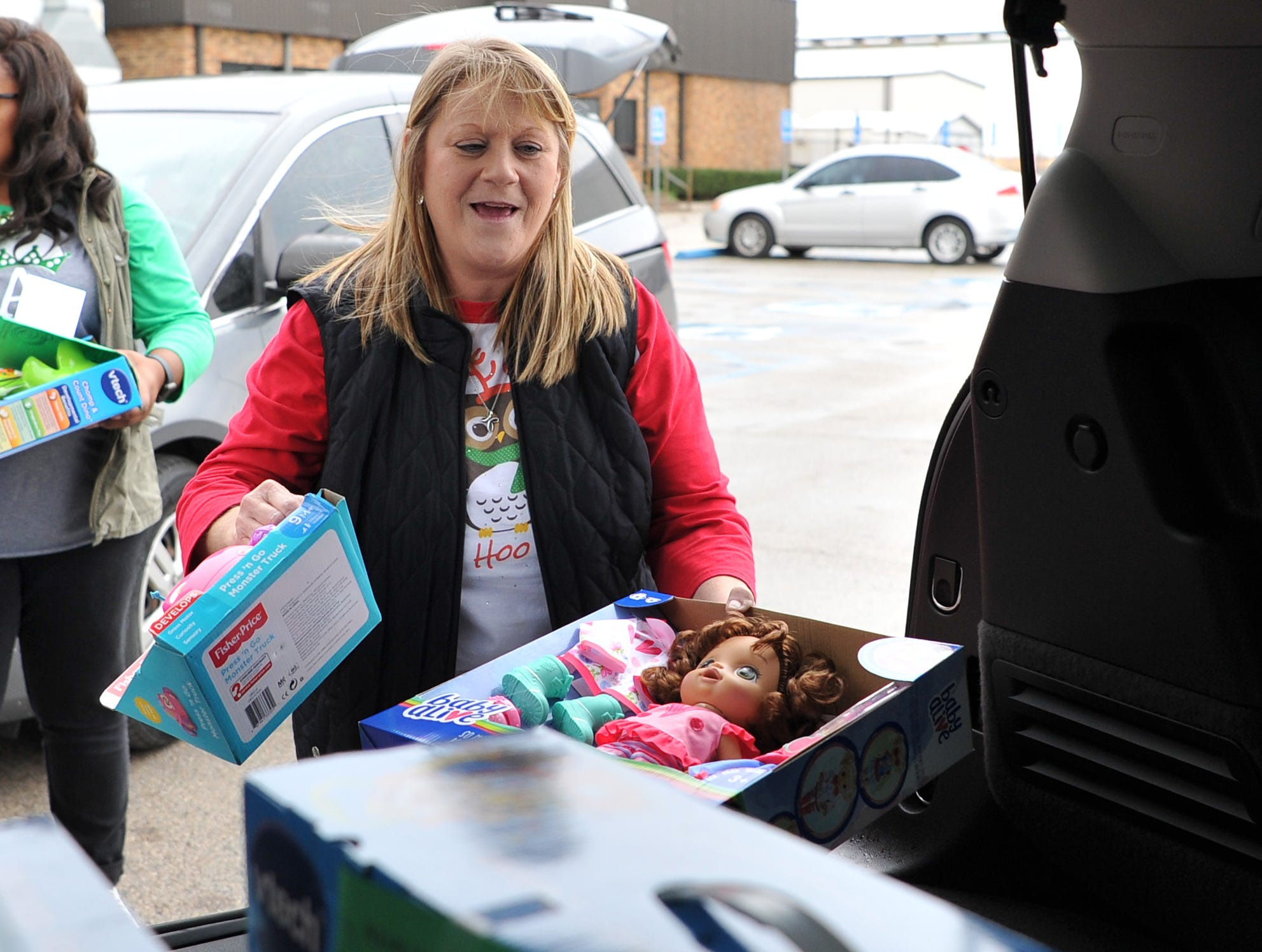 Child Care Partners Kelly Davis helps load donated toys from Alcoa employees Thursday afternoon. Davis said a phone 16-years-ago to a human resource specialist Elissa Depew at Alcoa has put a lot of smiles on local Child Care Partners kids' faces during the Christmas season.