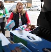 Child Care Partners Kelly Davis helps load donated toys from Acronic employees Thursday afternoon. Davis said a phone 16-years-ago to a human resource specialist Elissa Depew at Acronic has put a lot of smiles on local Child Care Partners kids faces during the Christmas season.