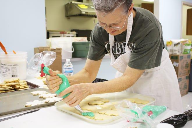 PAWS President Teresa Hildebrand decorates Christmas tree cookies for the non-profit's Cookie Walk on Dec. 8.
