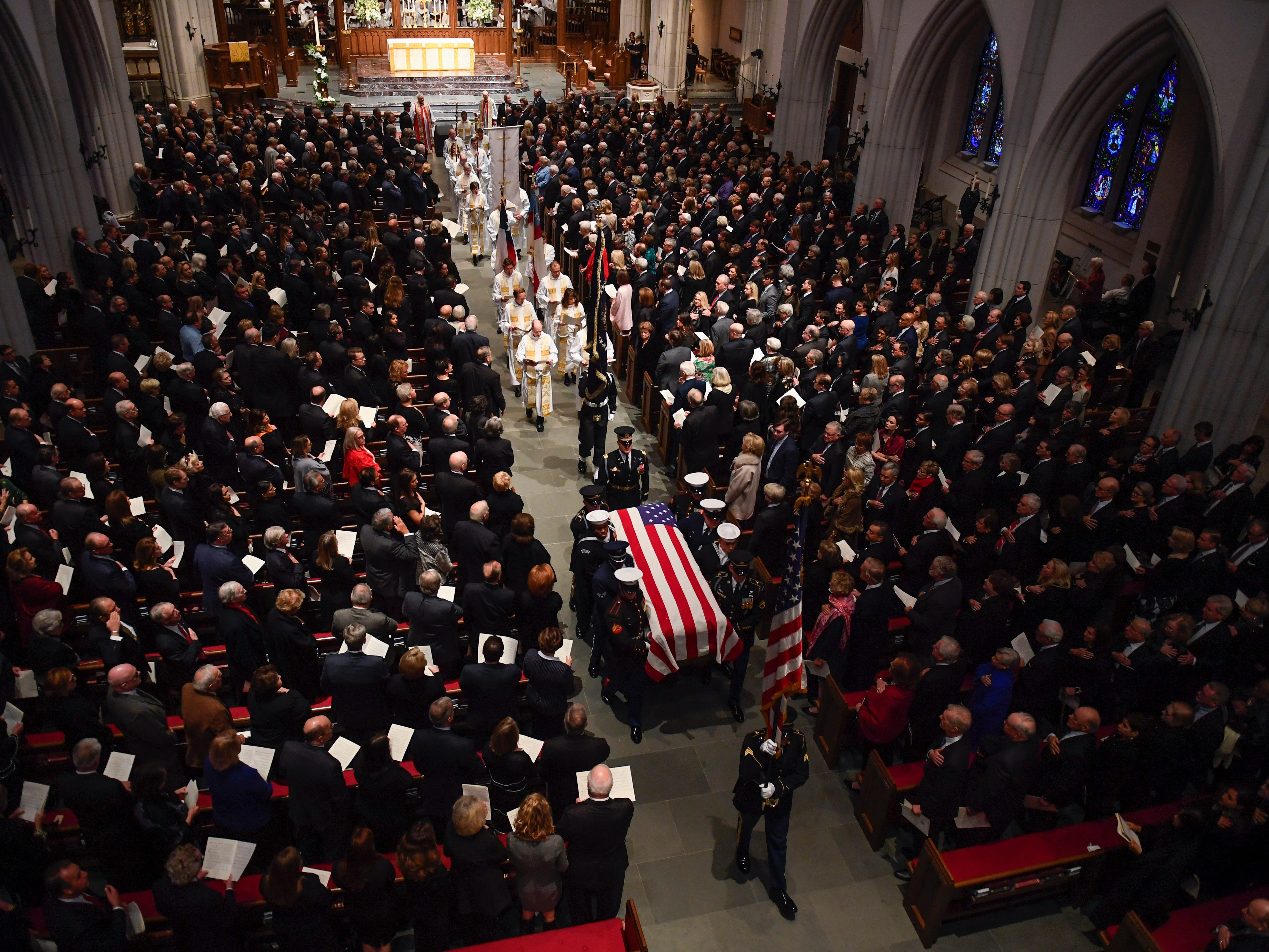 The flag-draped casket of former President George H.W. Bush is carried by a joint services military honor guard out of St. Martin's Episcopal Church Thursday, Dec. 6, 2018, in Houston.