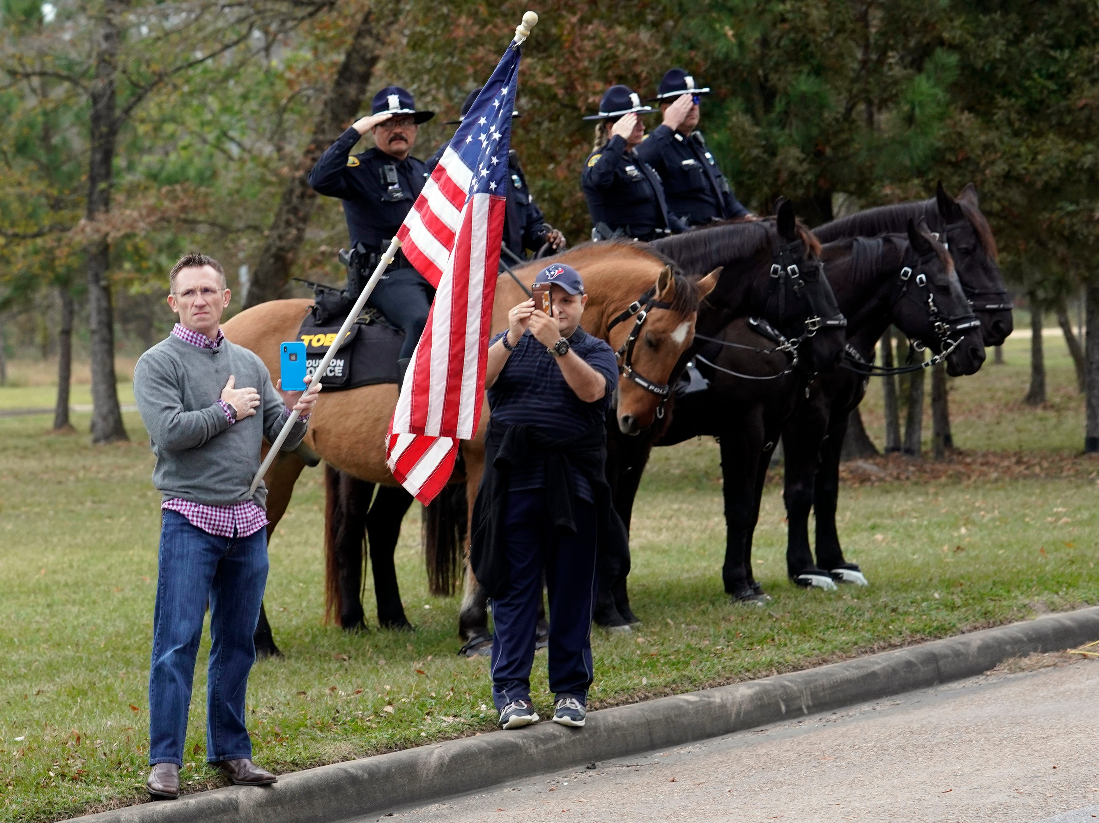 People line the road as the hearse carrying the flag-draped casket of former President George H.W. Bush heads to the Union Pacific train facility on Dec. 6, 2018 in Houston, Texas.
