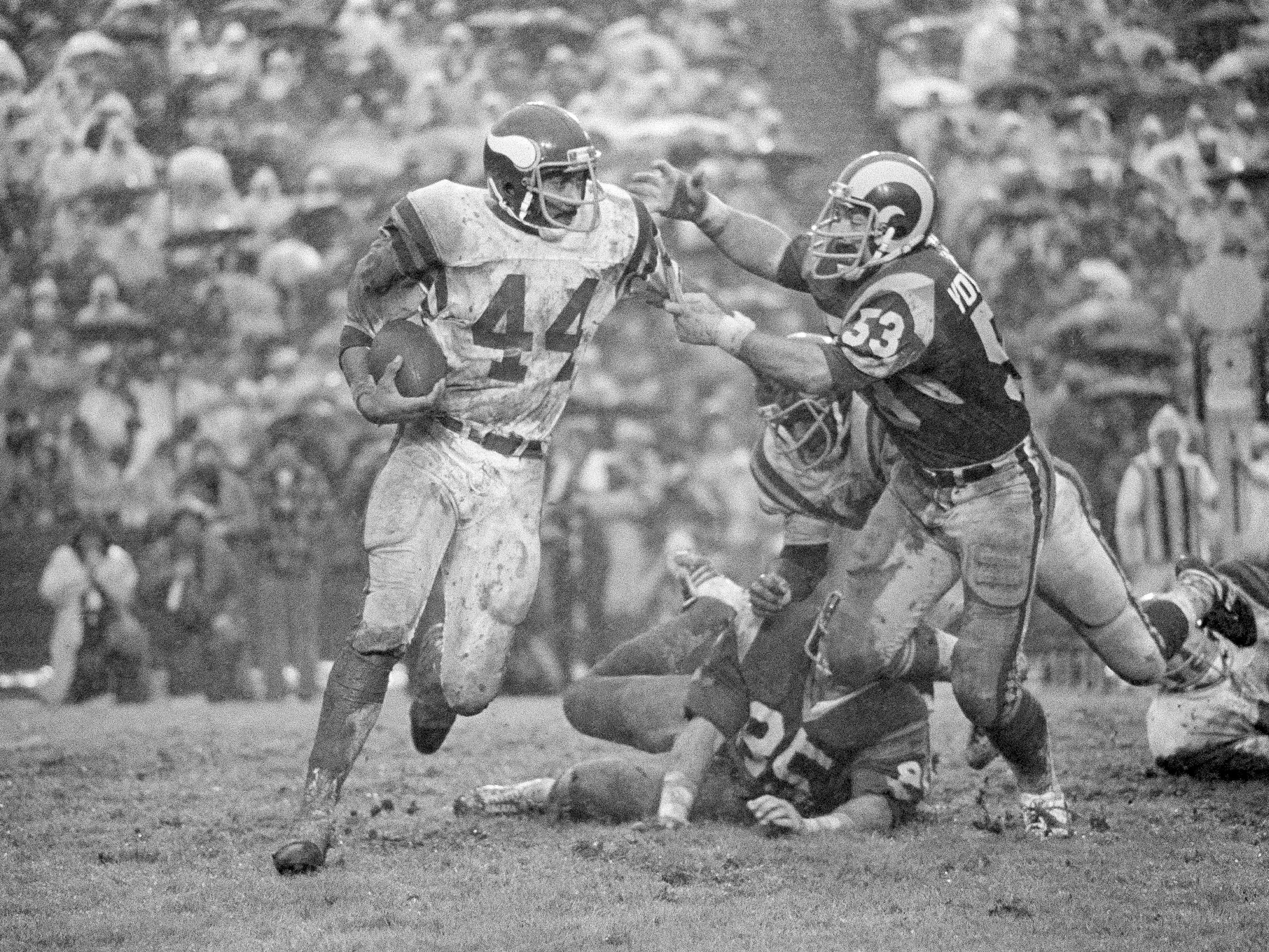 "Dec. 27, 1977: Minnesota Vikings running back Chuck Foreman (44) swings to get away from the Los Angeles Rams' Jim Youngblood during the rain-soaked NFC divisional playoff game in Los Angeles that would become known as the ""Mud Bowl."" The Vikings won the game, 14-7, that was played at the L.A. Coliseum."