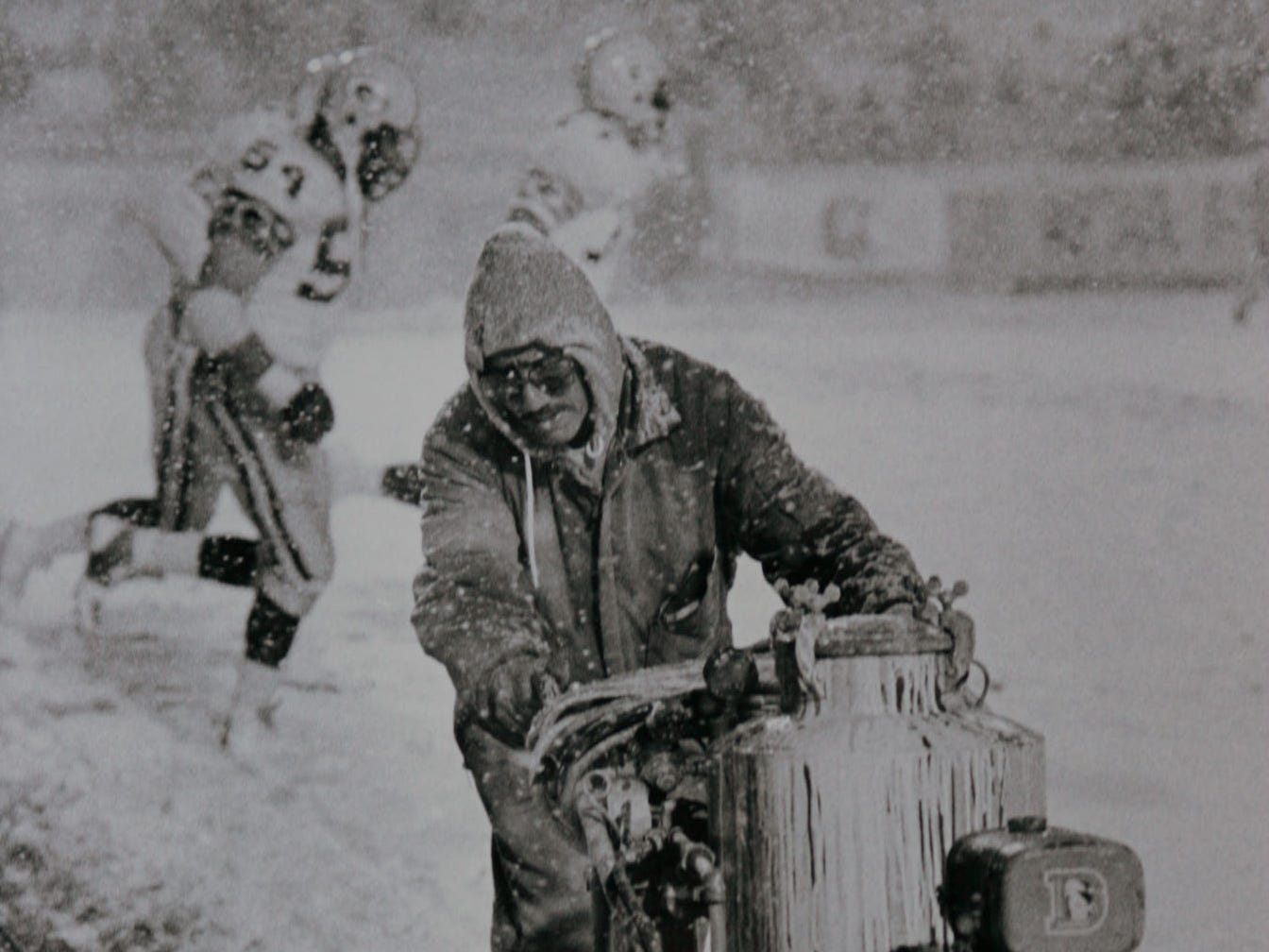 Oct. 15, 1984: A maintenance worker paints orange stripes on the field as more than 10 inches of snow falls during the Monday Night Football game between the Green Bay Packers and Denver Broncos at Mile High Stadium.  The Broncos won the game, 17-14.
