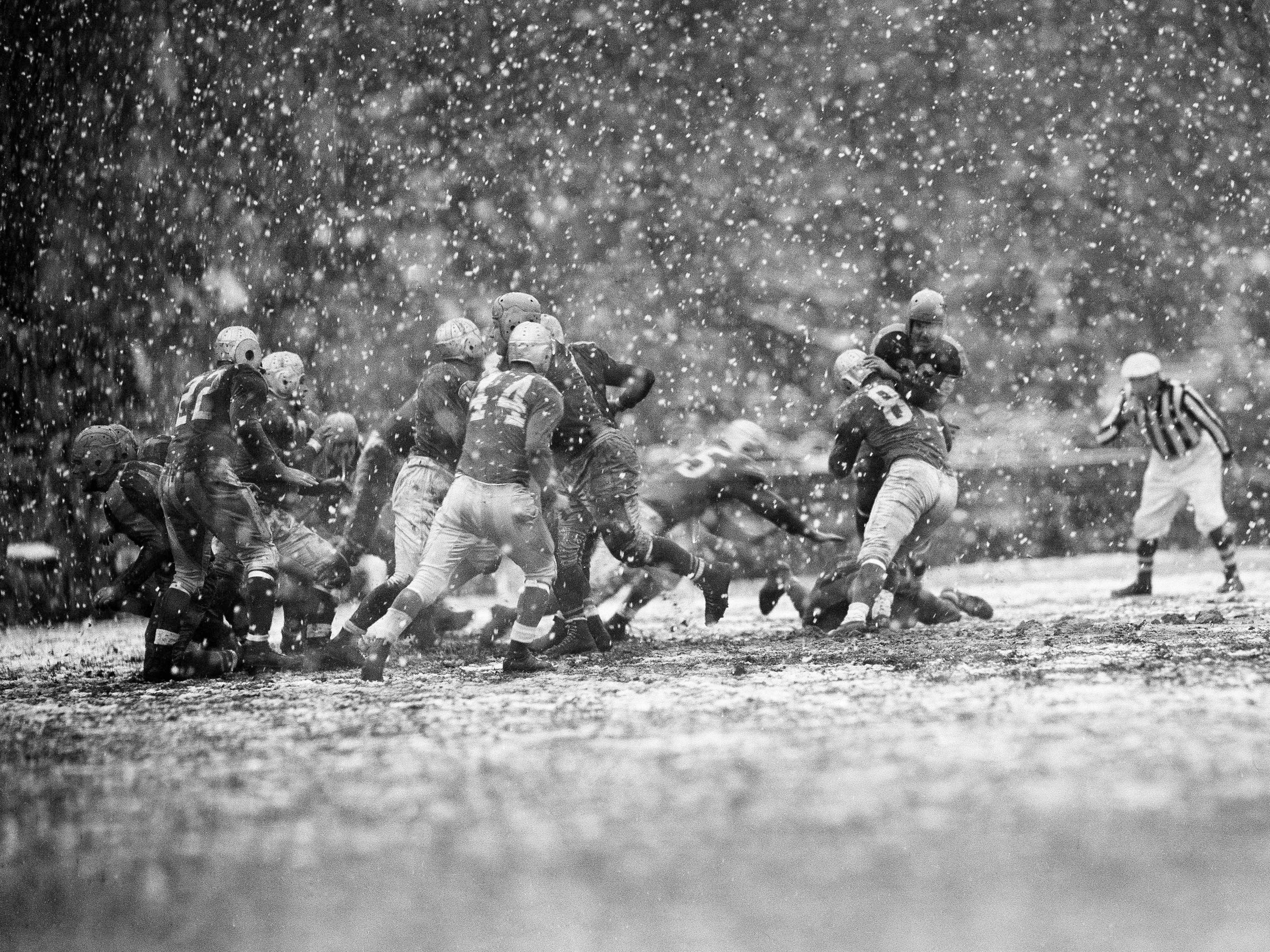 Nov. 4, 1945: Boston Yanks halfback Johnny Grigas is stopped for no gain when the Detroit Lions' Jack Matheson, (82) tackles during a game played in heavy snow at Fenway Park in Boston.  The Lions won the game, 10-9.