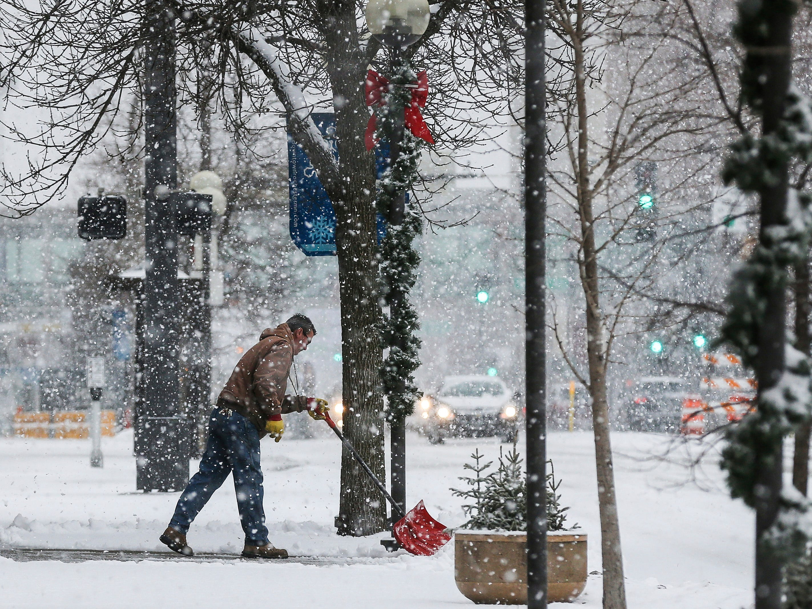 Ron Ruport, owner of Old Rooster Antiques, shovels in front of his shop as heavy snow falls Dec. 1, 2018, along Broadway Avenue North in downtown Rochester, Minn.