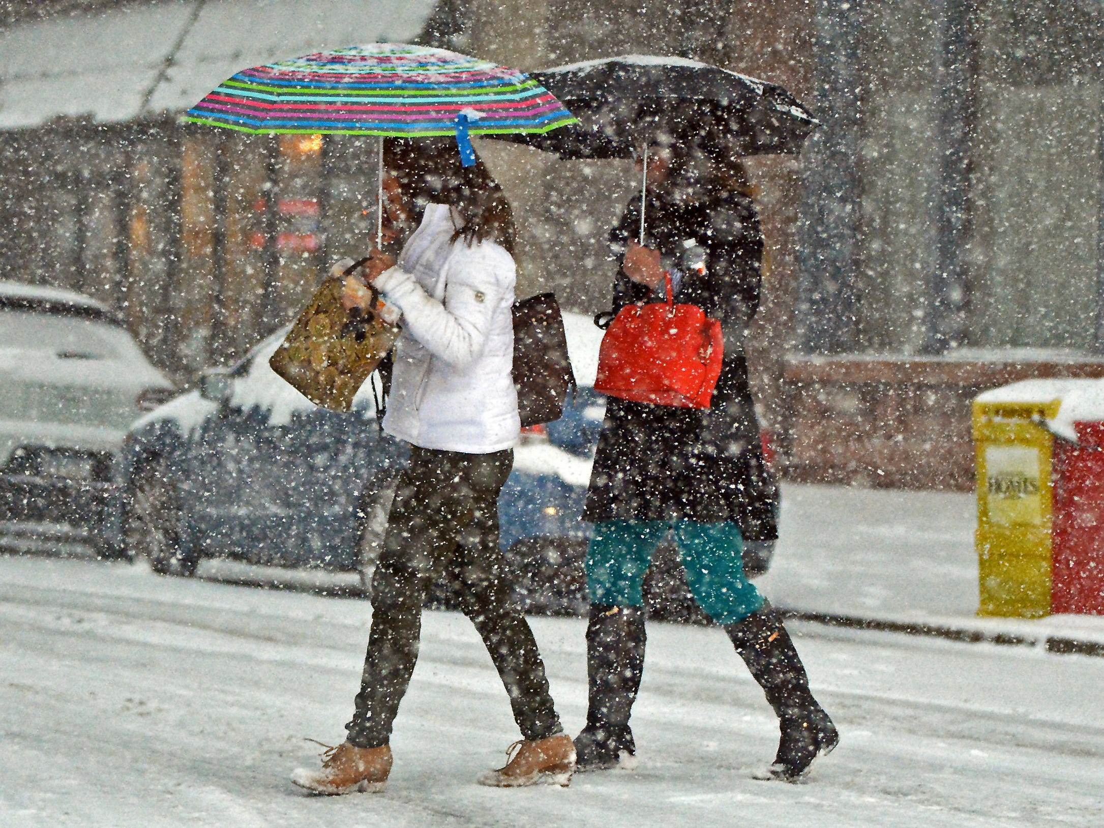 Women were armed with their umbrella's as they cross a street during an autumn snow storm on Nov. 15, 2018, in downtown Scranton, Pa.