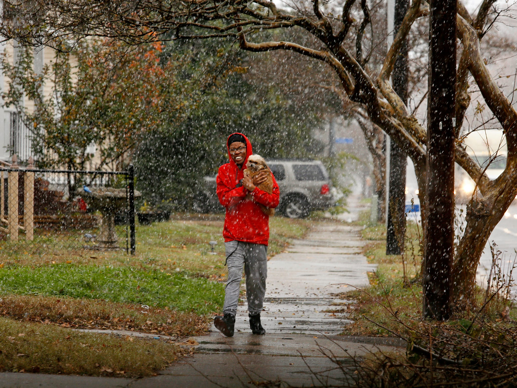 Josef Dowling, sheltering Dallas from the snow, walks in Norfolk, Va., on Dec. 5, 2018.