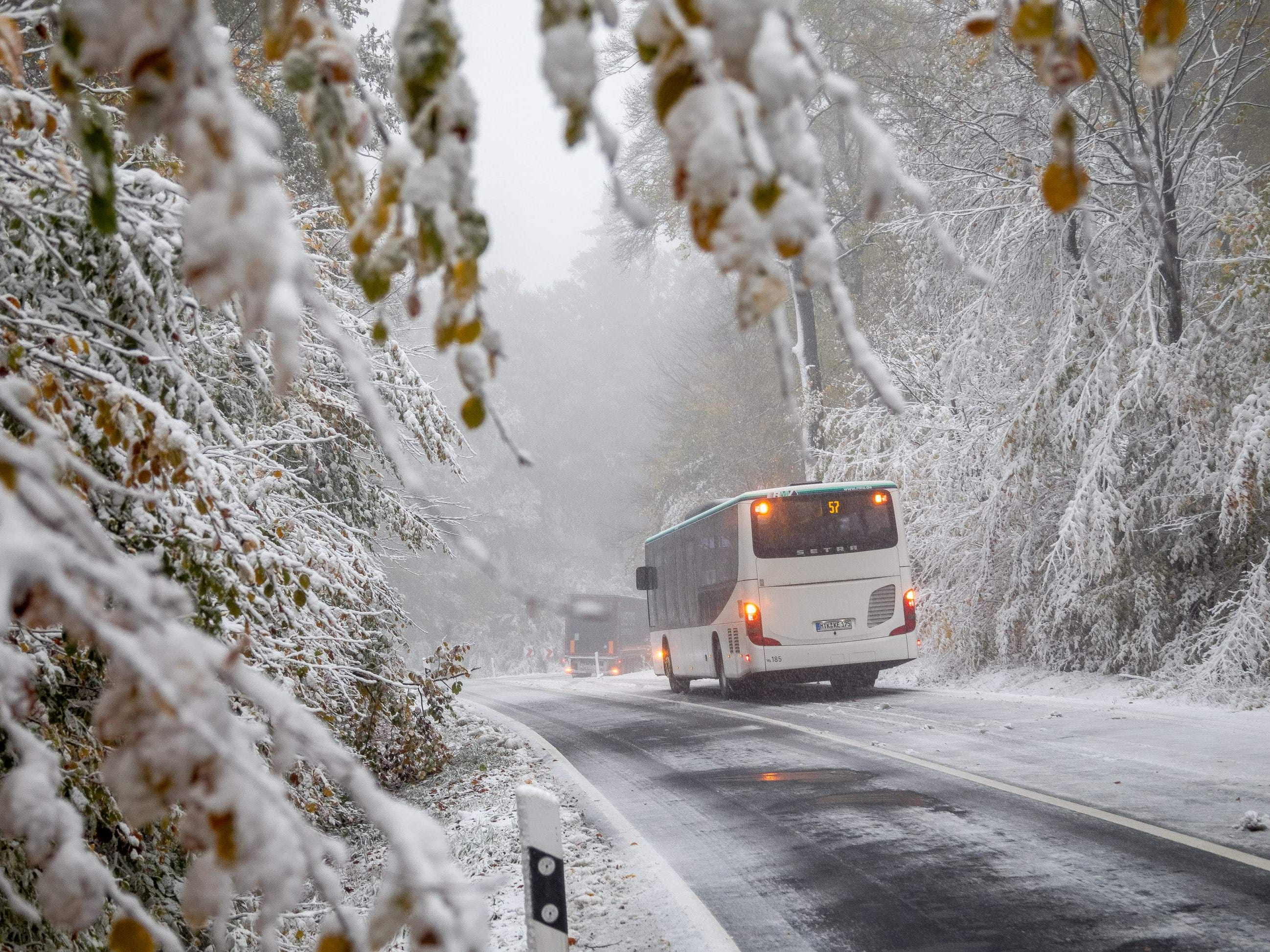 A bus and a truck drive through the first snow near Schmitten in the Taunus mountains, central Germany, on Oct. 30, 2018.