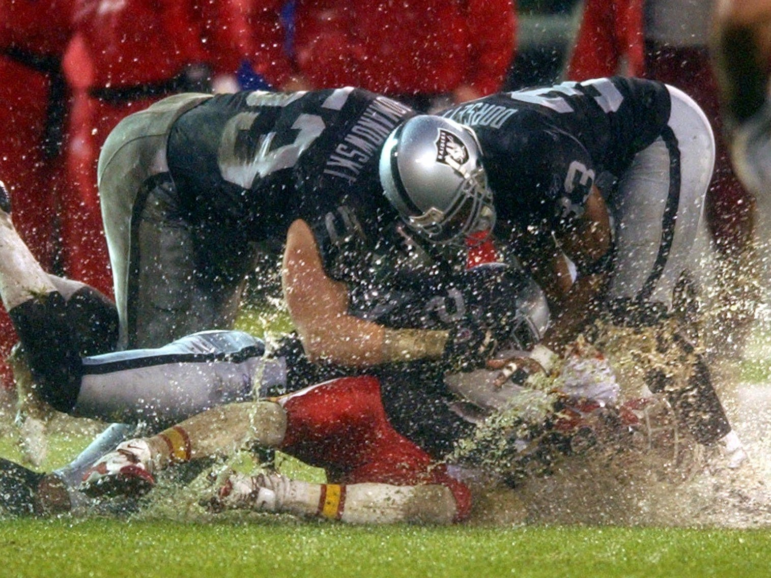 Dec. 28, 2002: Kansas City Chiefs wide receiver Johnnie Morton is smothered by Oakland Raiders defenders Bill Romanowski, Anthony Dorsett, right, and Terrance Shaw after catching a pass during the fourth quarter in Oakland. The Raiders won the game, 24-0.