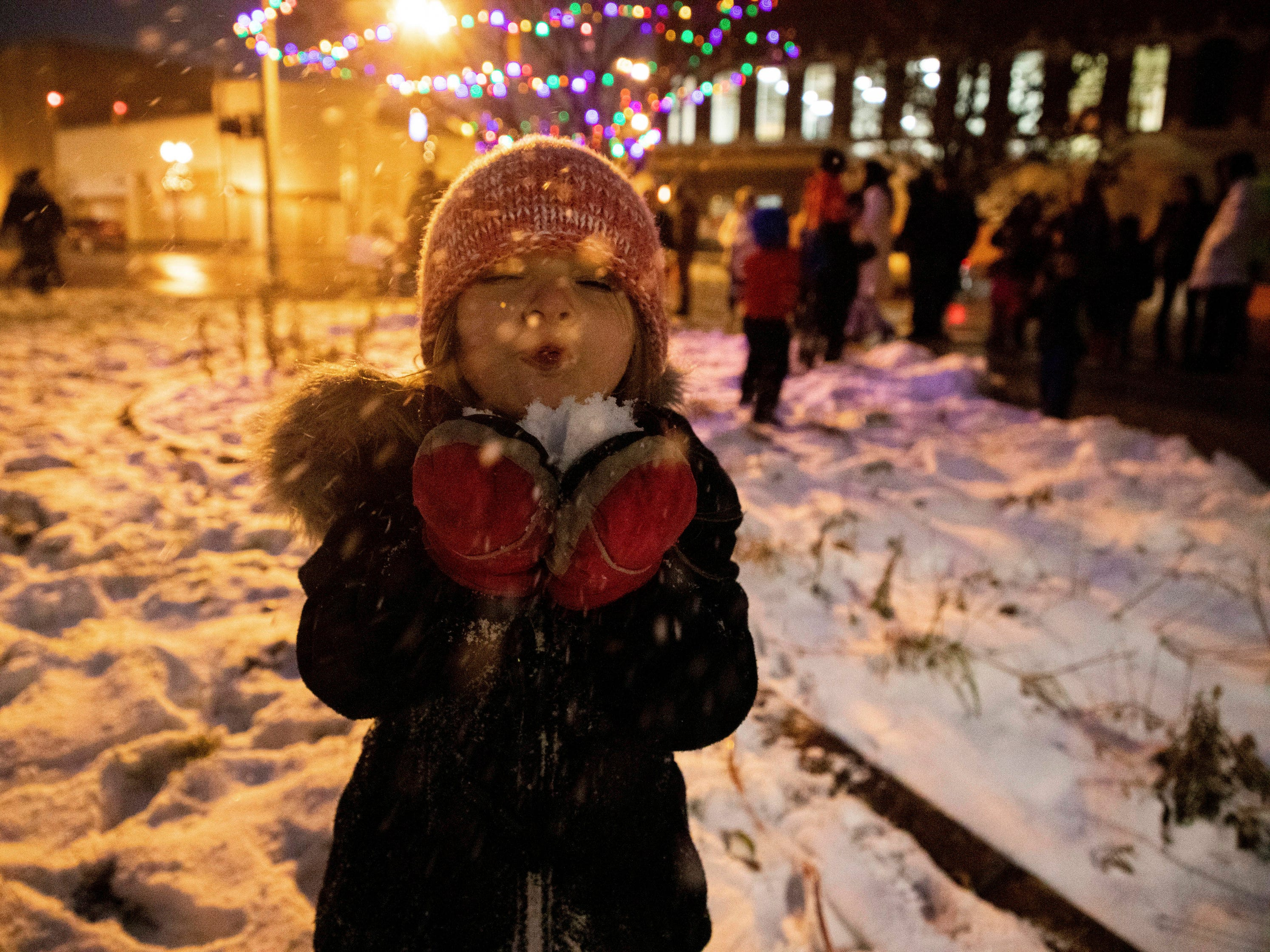Camrynn LeMay, 4, blows snow into the air during the Christmas tree lighting celebration on Nov. 29, 2018, in downtown Flint, Mich.