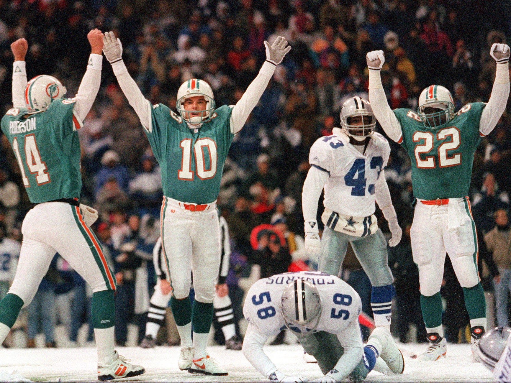 Nov. 25, 1993: Miami Dolphins quarterback Doug Pederson (14), kicker Pete Stoyanovich (10) and James Saxon (22) celebrate after Stoyanovich kicked the winning field goal with 3 seconds remaining in Miami's 16-14 win over the Dallas Cowboys at Texas Stadium on Thanksgiving Day.