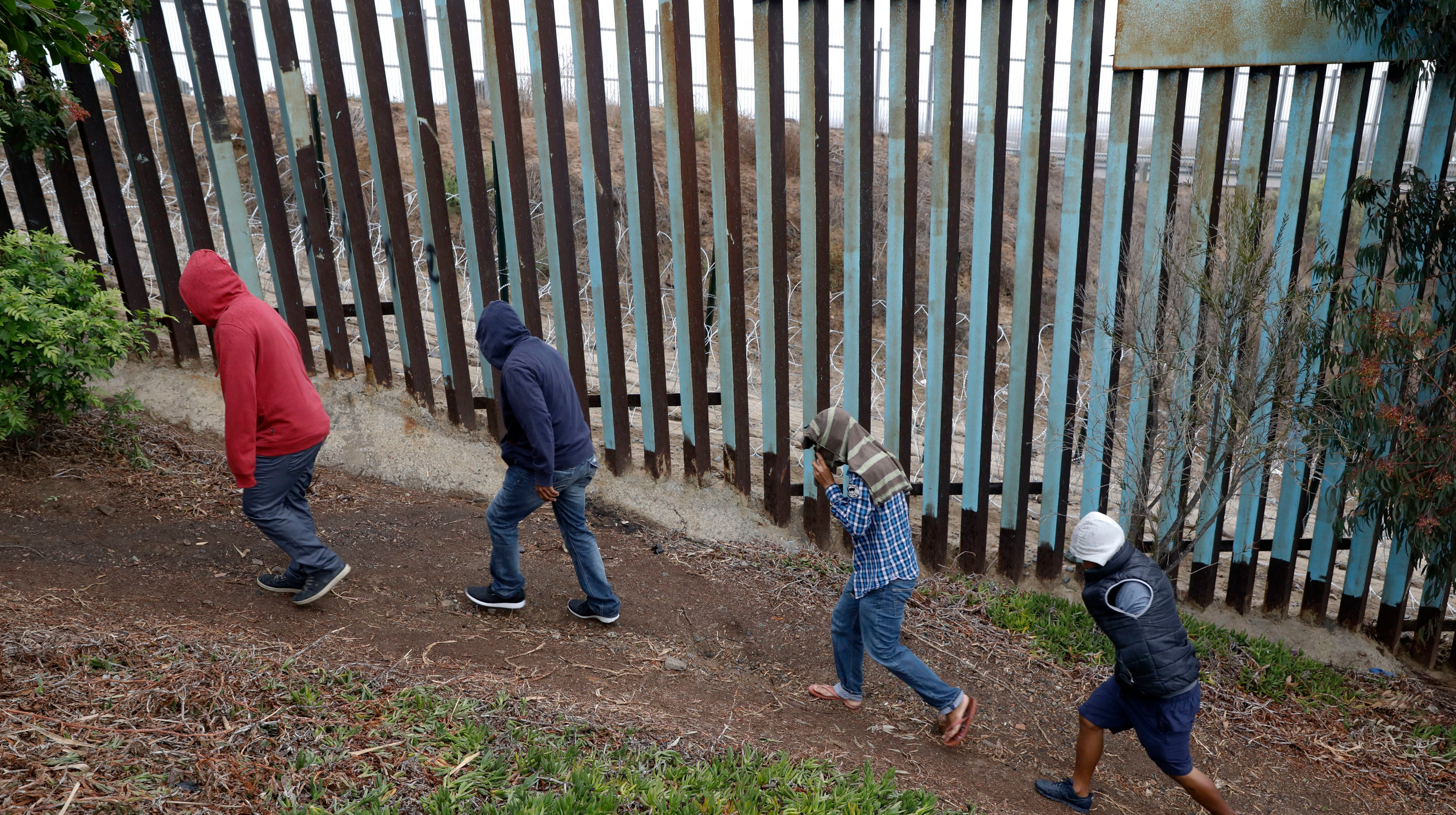 Central American migrants walk along the U.S. border fence looking for places they might be able to cross, in Playas de Tijuana, Mexico, Wednesday, Dec. 5, 2018.
