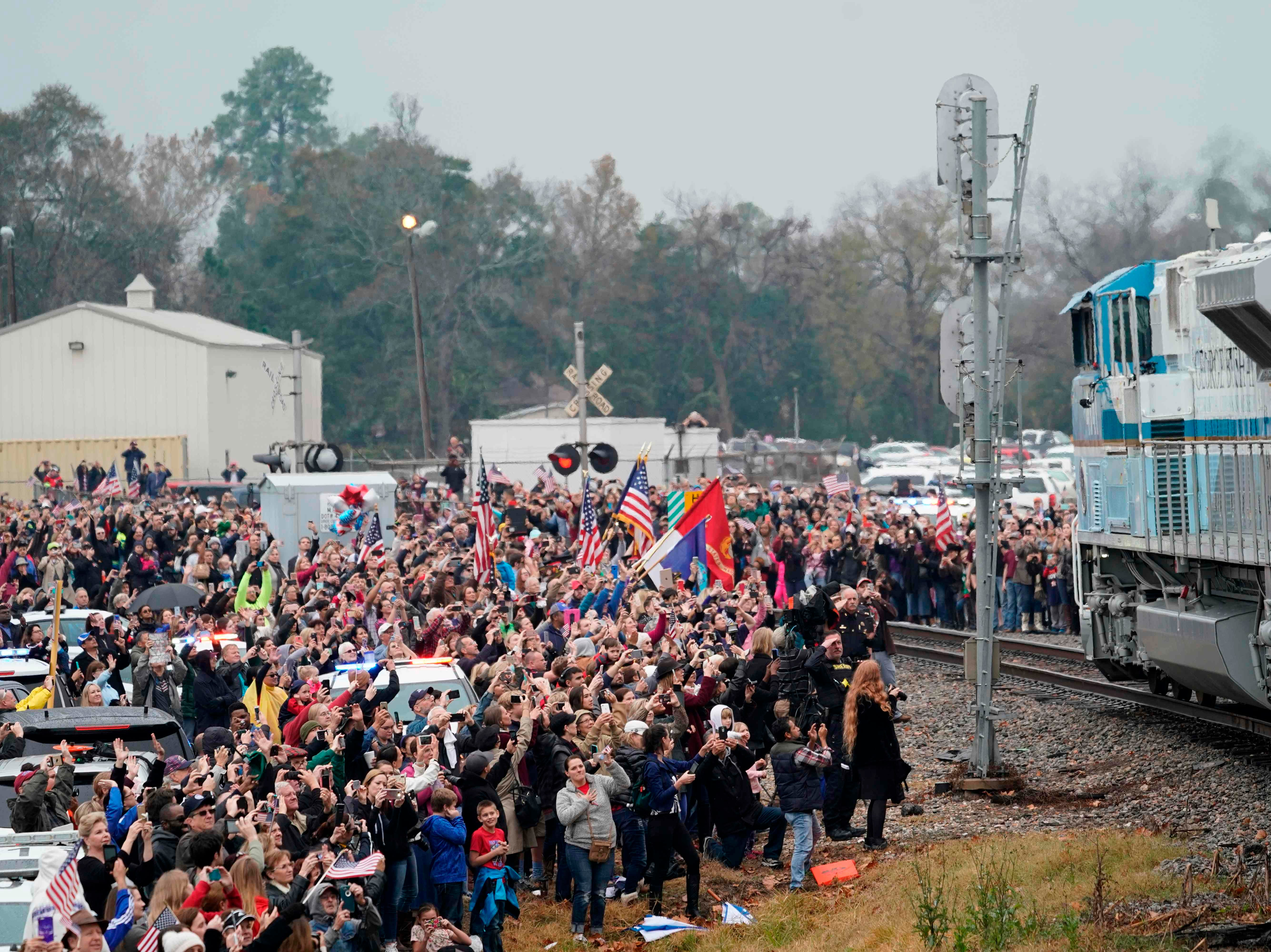 People pay their respects as the train carrying the casket of former US President George H.W. Bush passes on Dec. 6, 2018, along the route from Spring to College Station, Texas.
