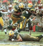 Packers running back Edgar Bennett hurdles teammate Aaron Taylor for a touchdown in Green Bay's 35-14 win in an NFC divisional playoff game against the San Francisco 49ers in 1997.