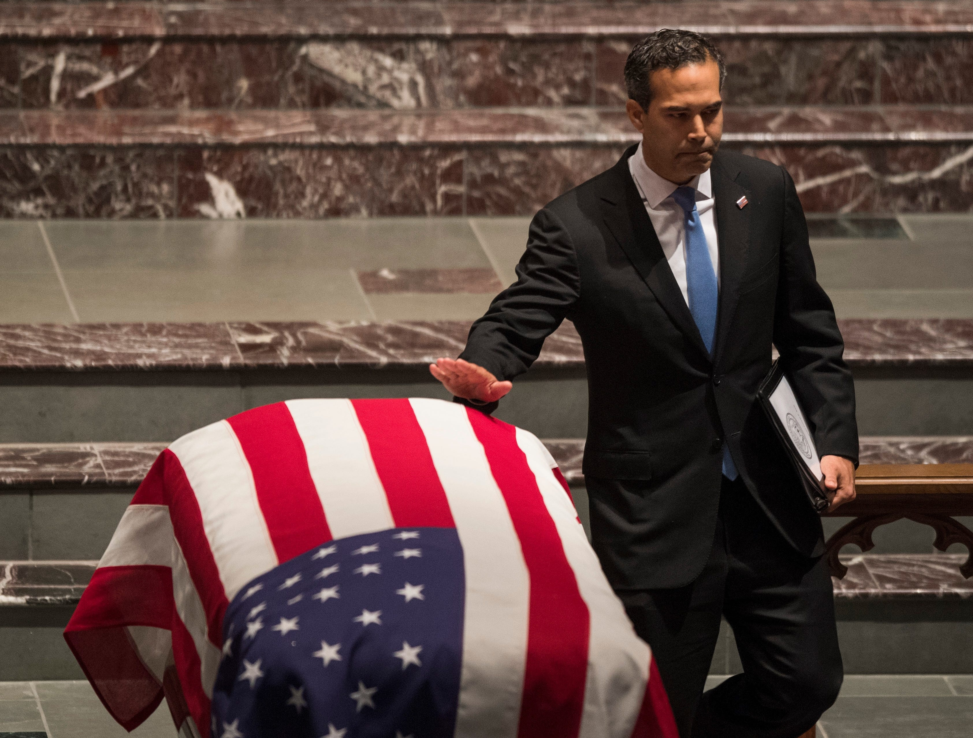 George P. Bush passes the flag-draped casket of former President George H.W. Bush after speaking at the funeral service at St. Martin's Episcopal Church in Houston, Thursday, Dec. 6, 2018.
