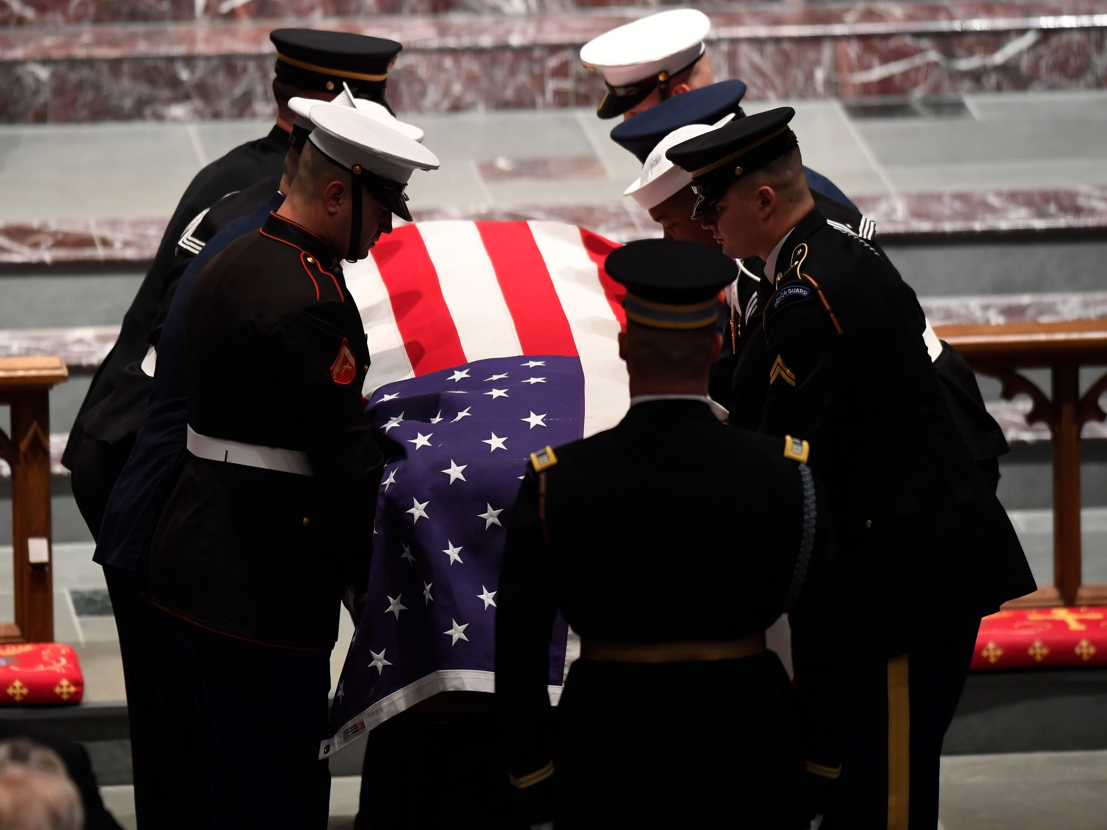 The flag-draped casket of former President George H.W. Bush is carried by a joint services military honor guard and placed in St. Martin's Episcopal Church Thursday, Dec. 6, 2018, in Houston.