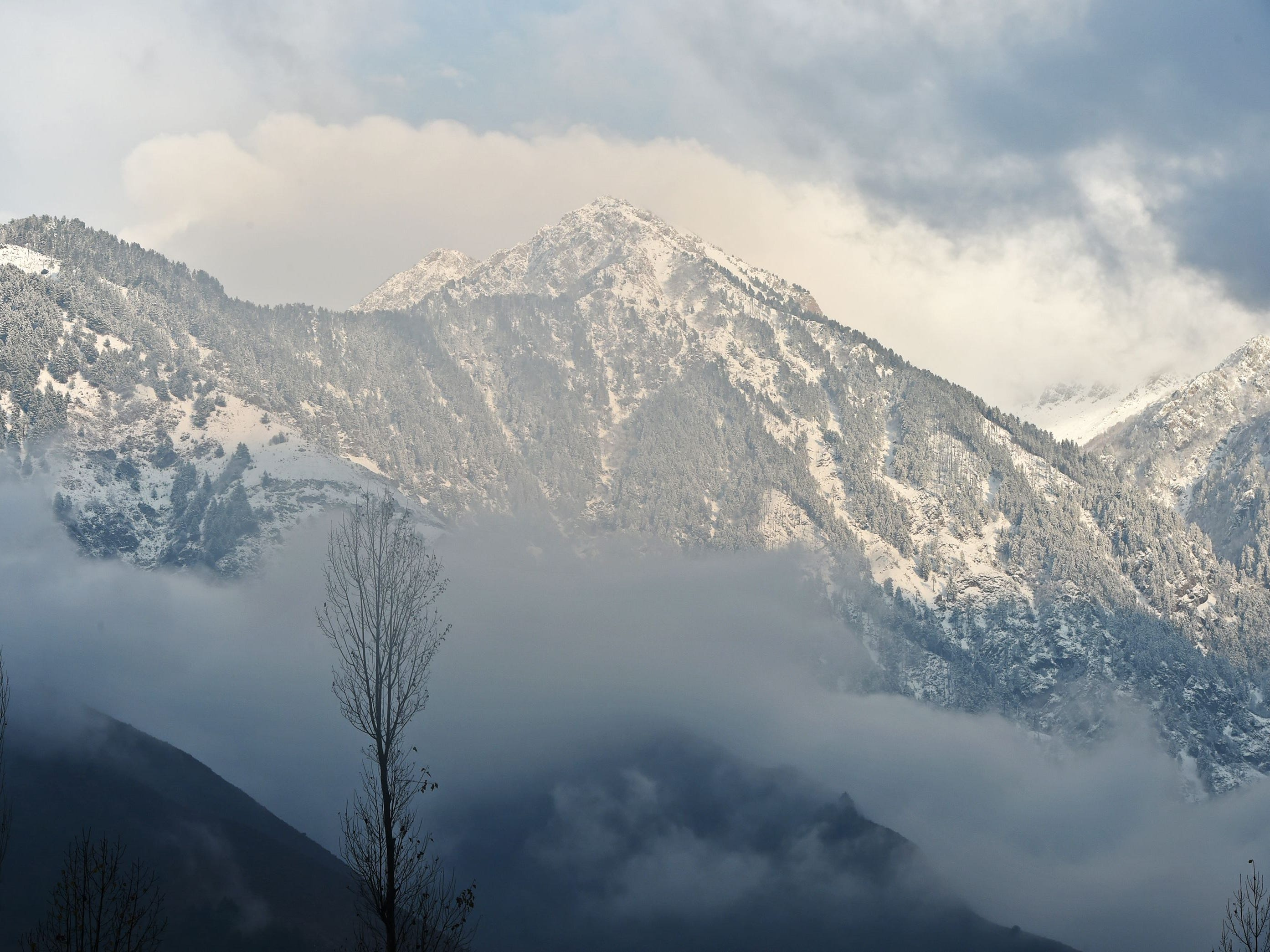 Snow covered mountains are seen during a cold and rainy day on the outskirts of Srinagar, India on Nov. 14, 2018.