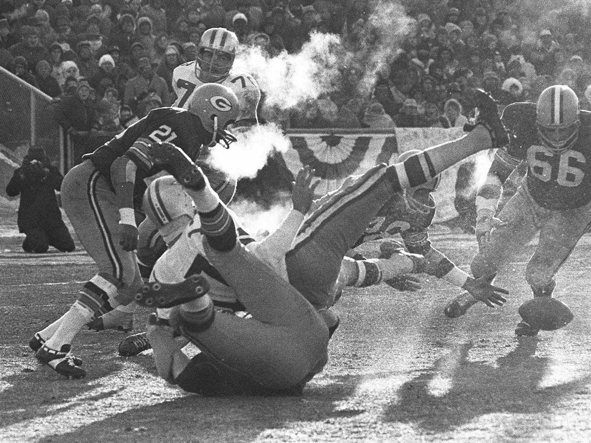 "Dec. 31, 1967: Players spill in all directions as a fumble occurs during the ""Ice Bowl"" at Lambeau Field. The Green Bay Packers defeated the Dallas Cowboys, 21-17, in one of the most famous games in NFL history."