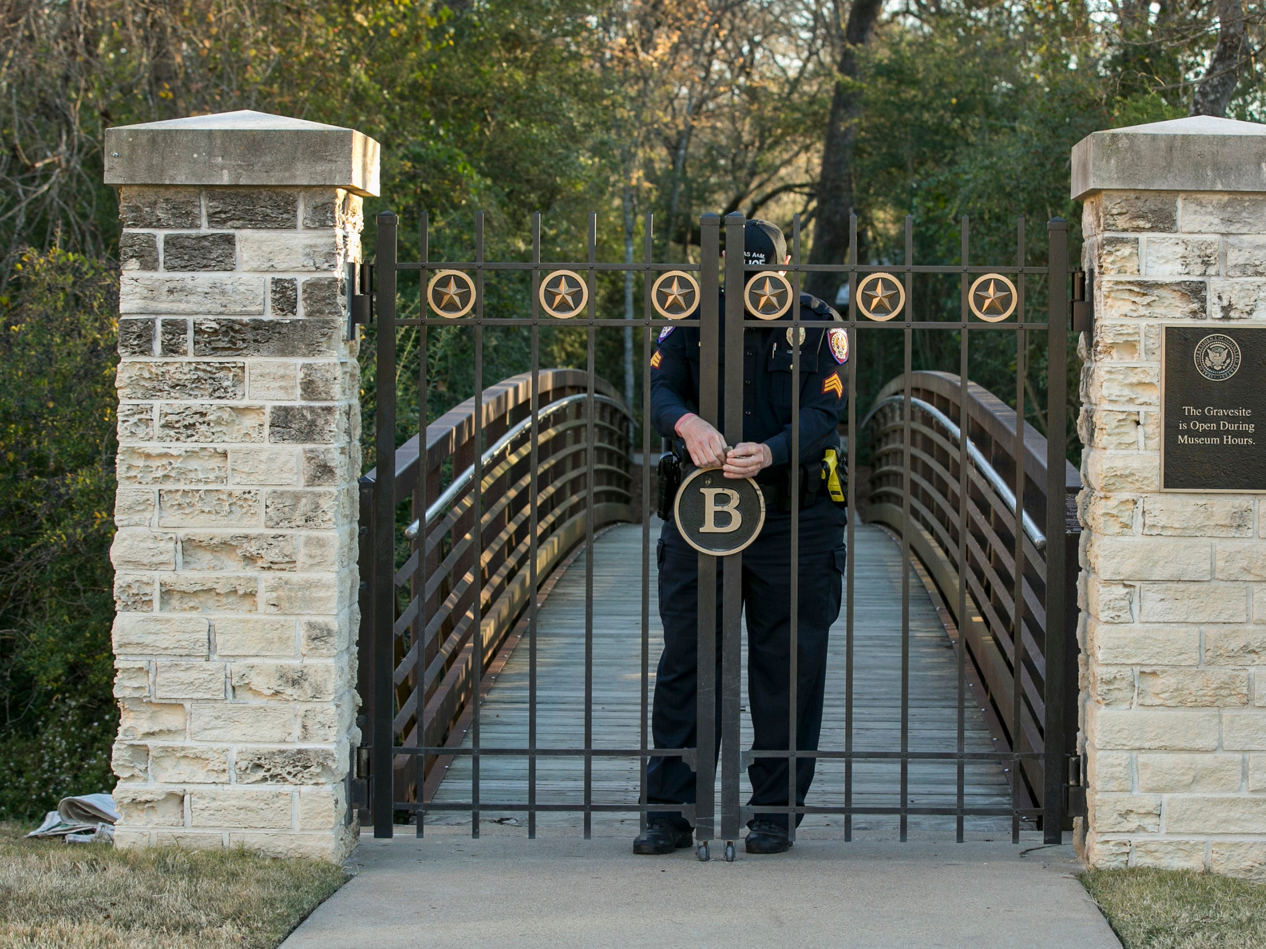 Sgt. Wayne Goldwater of the Texas A&M Police Department guards the burial site of George H.W. Bush and Barbara Bush at the George H.W. Bush Presidential Library at Texas A&M University in College Station, Texas, on Wednesday, Dec. 5, 2018.