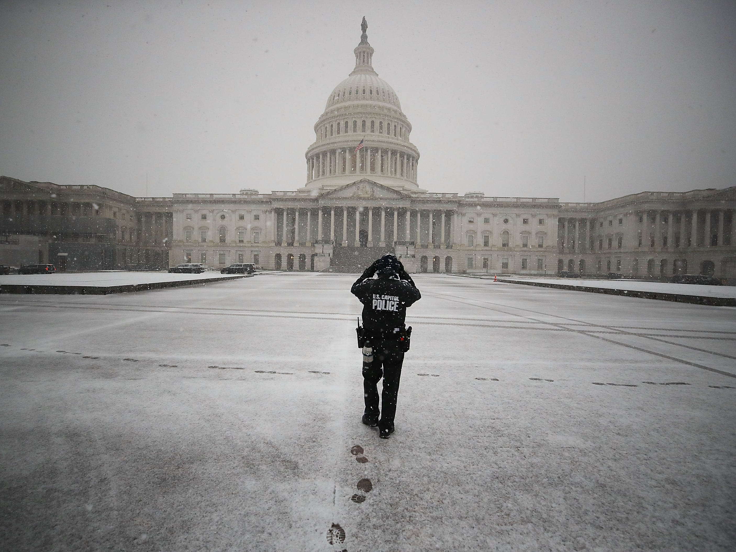 A U.S. Capitol Police Officer patrols the Capitol plaza as snow falls on Nov. 15, 2018 in Washington, D.C.