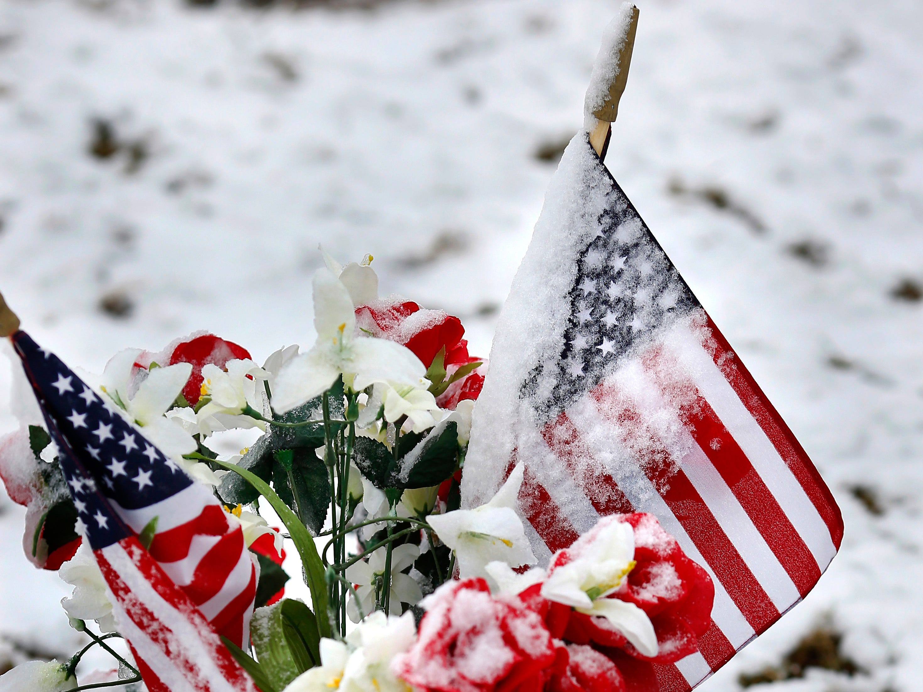 American flags, some partially obscured by snow, decorate a grave in observance of Veterans Day at Arlington Memory Gardens in Midwest City, Okla. on Nov. 12, 2018.