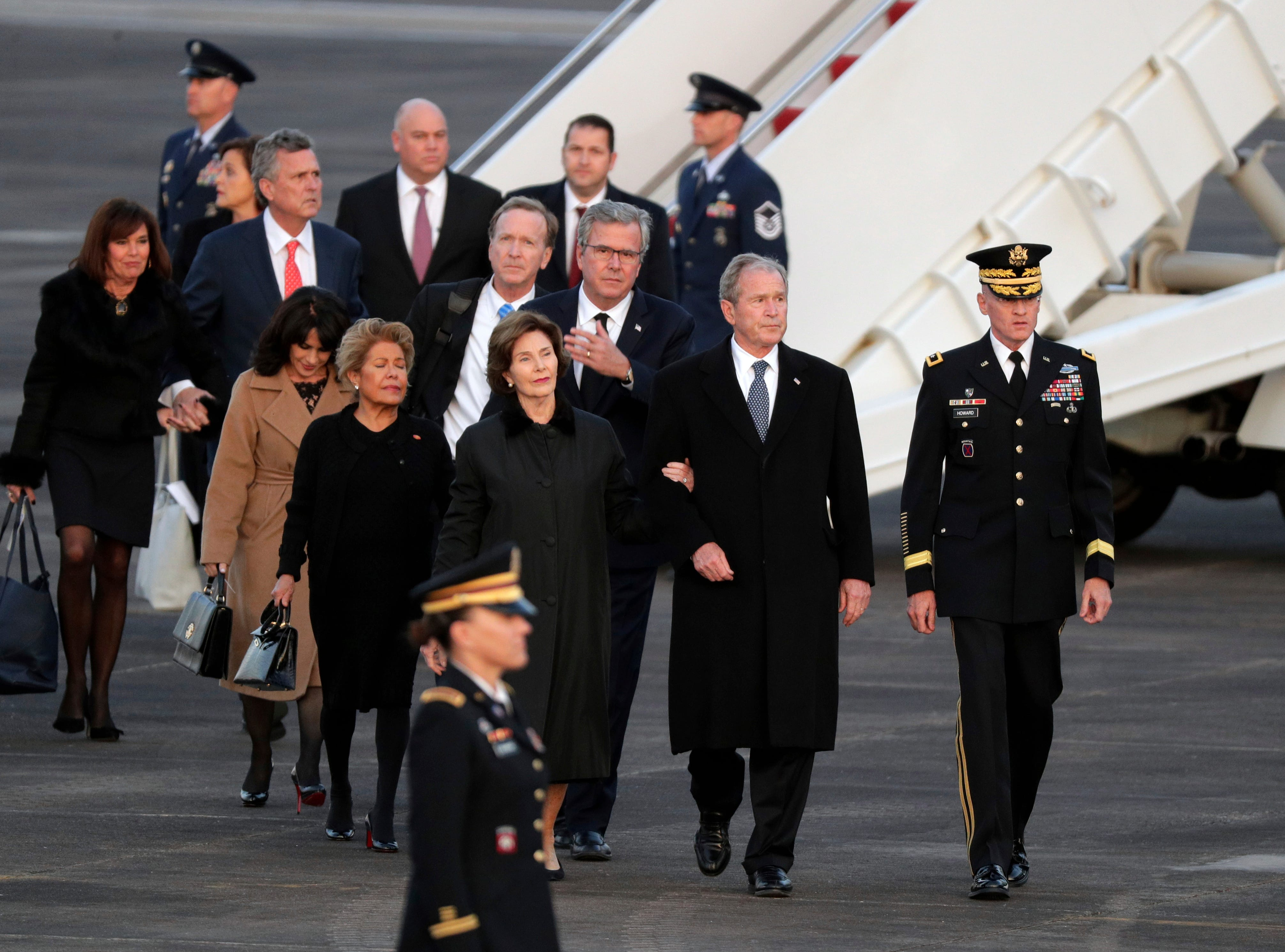 Former President George W. Bush and family members of former President George H.W. Bush walk off Special Air Mission 41 as the casket arrives at Ellington Field Wednesday, Dec. 5, 2018, in Houston.