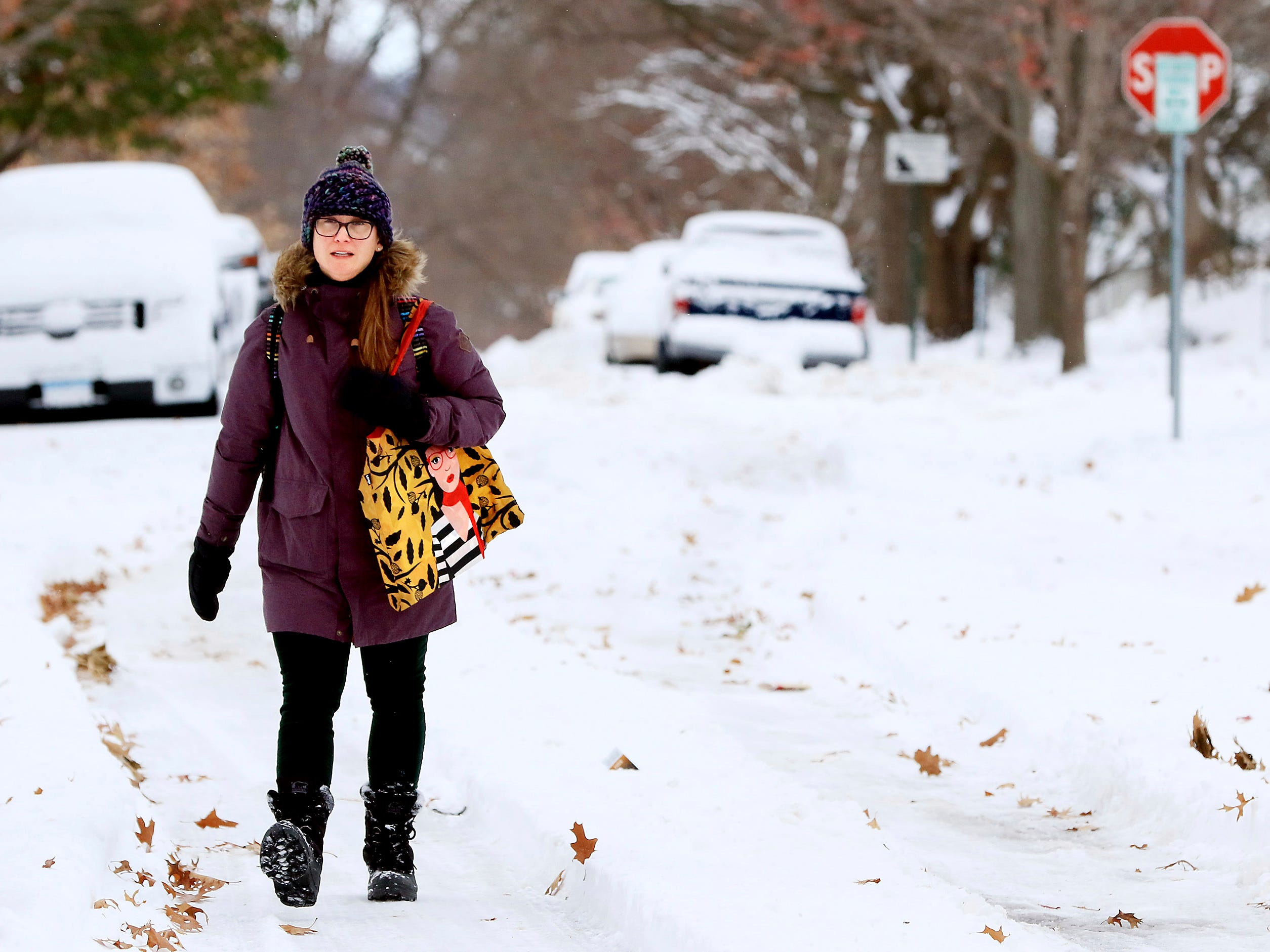 Avoiding snow covered sidewalks St. Ambrose University librarian Jennifer Smith walks along Ripley Street in Davenport, Iowa, on her way to work Nov. 26, 2018.