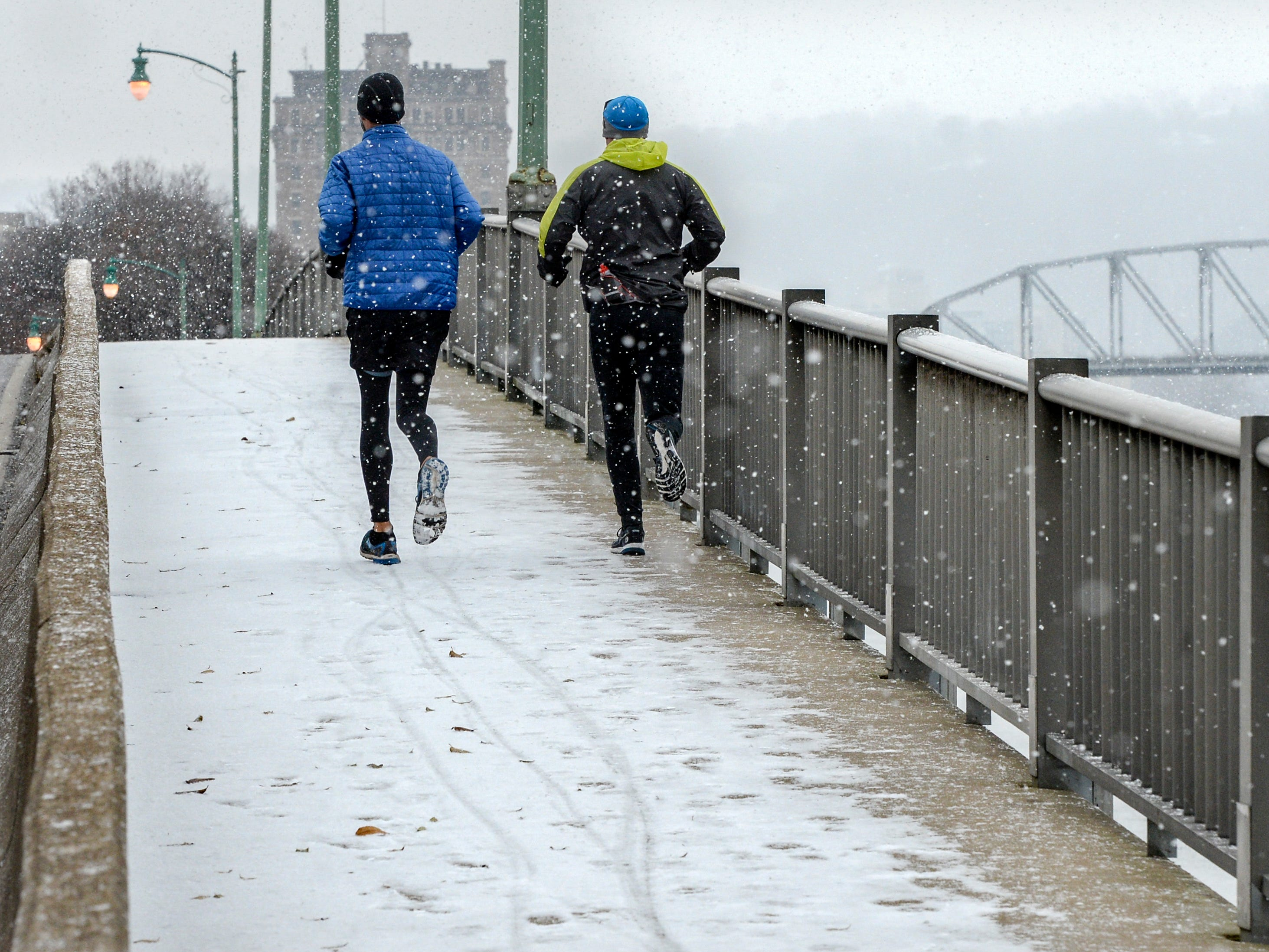 Runners cross the Elk River Bridge in Charleston, W.V., during a snow squall on Nov. 28, 2018.