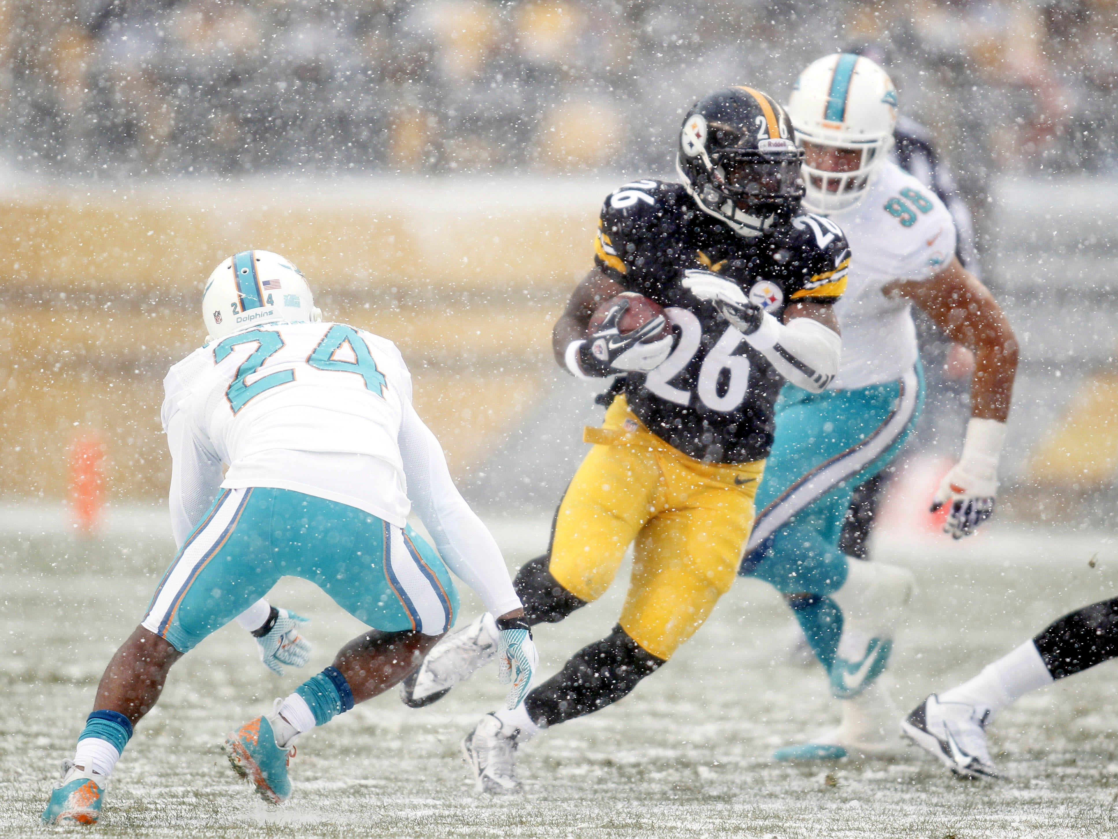 Dec. 8, 2013: Pittsburgh Steelers running back Le'Veon Bell carries the ball as Miami Dolphins cornerback Dimitri Patterson (24) and defensive tackle Jared Odrick (98) pursue during the first quarter at Heinz Field. The Dolphins won the game, 34-28.