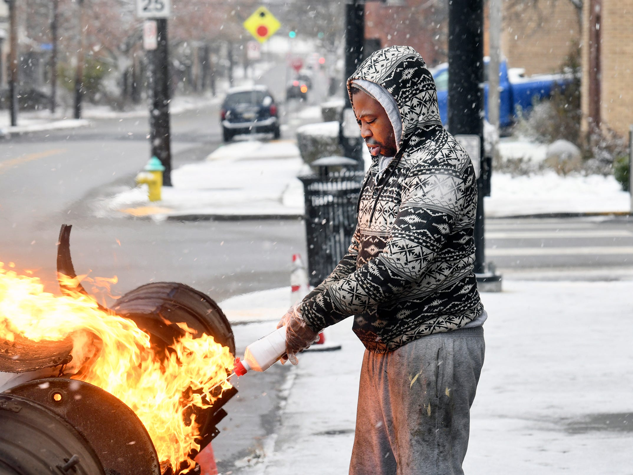 Aaron Bevins fires up the coals as snow falls on Nov. 27, 2018, at The Dream barbecue restaurant on N. Braddock Avenue in Pittsburgh neighborhood, Homewood.