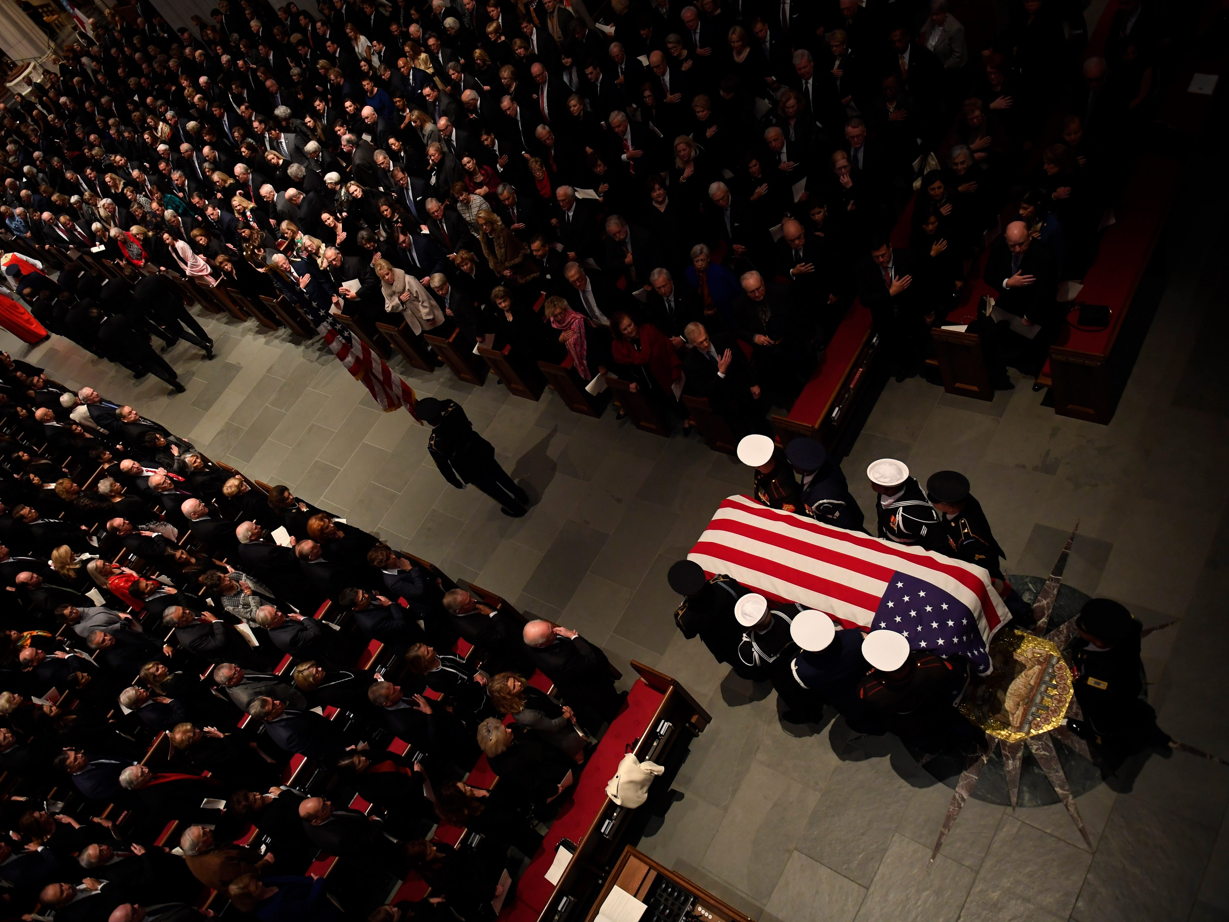The flag-draped casket of former President George H.W. Bush is carried by a joint services military honor guard into St. Martin's Episcopal Church Thursday, Dec. 6, 2018, in Houston.