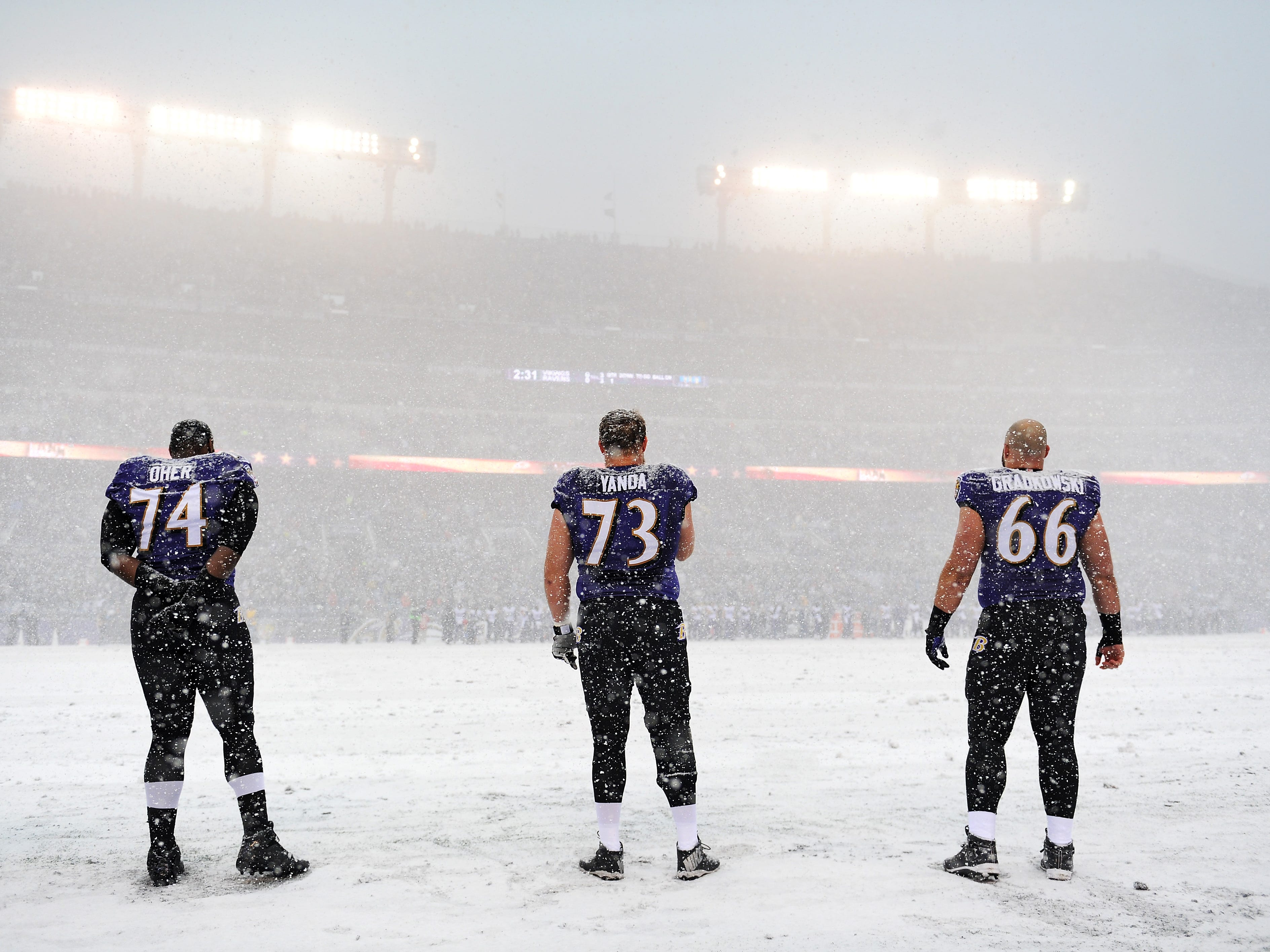 Dec. 20, 2013: The Baltimore Ravens' Michael Oher (74), Marshal Yanda (73) and Gino Gradkowski stand on the snow-covered field during the national anthem before playing the Minnesota Vikings at M&T Bank Stadium in Baltimore. The Ravens won the game, 29-26.