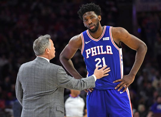 Philadelphia 76ers head coach Brett Brown talks with center Joel Embiid.