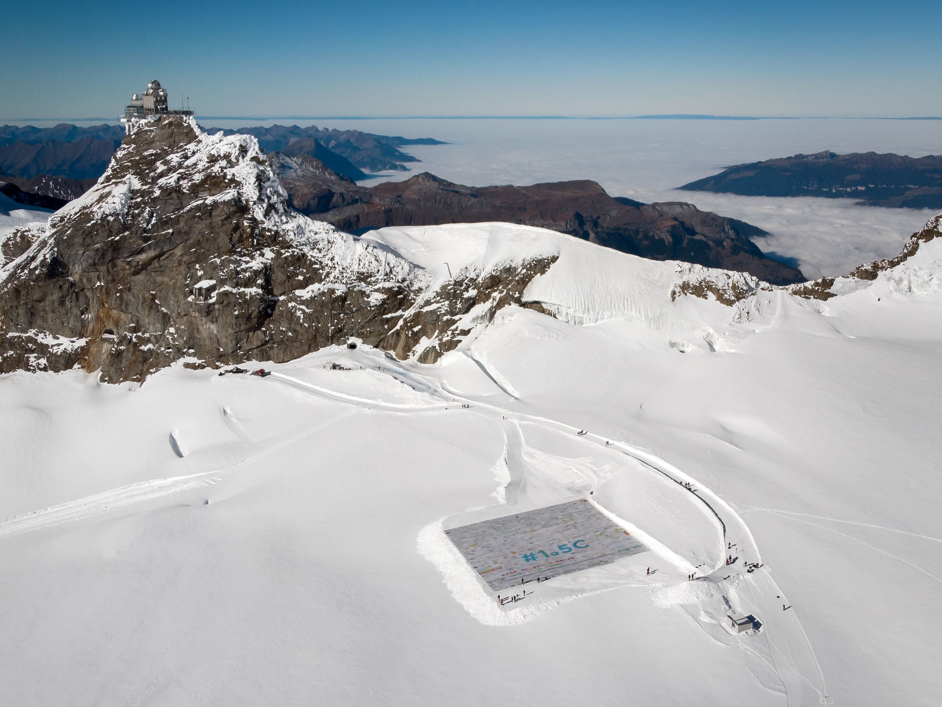 An aerial view shows a massive collage of 125,000 drawings and messages from children around the world about climate change seen rolled out on the Aletsch Glacier at an altitude of 3,400 meters near the Jungfraujoch in the Swiss Alps on Nov. 16, 2018.