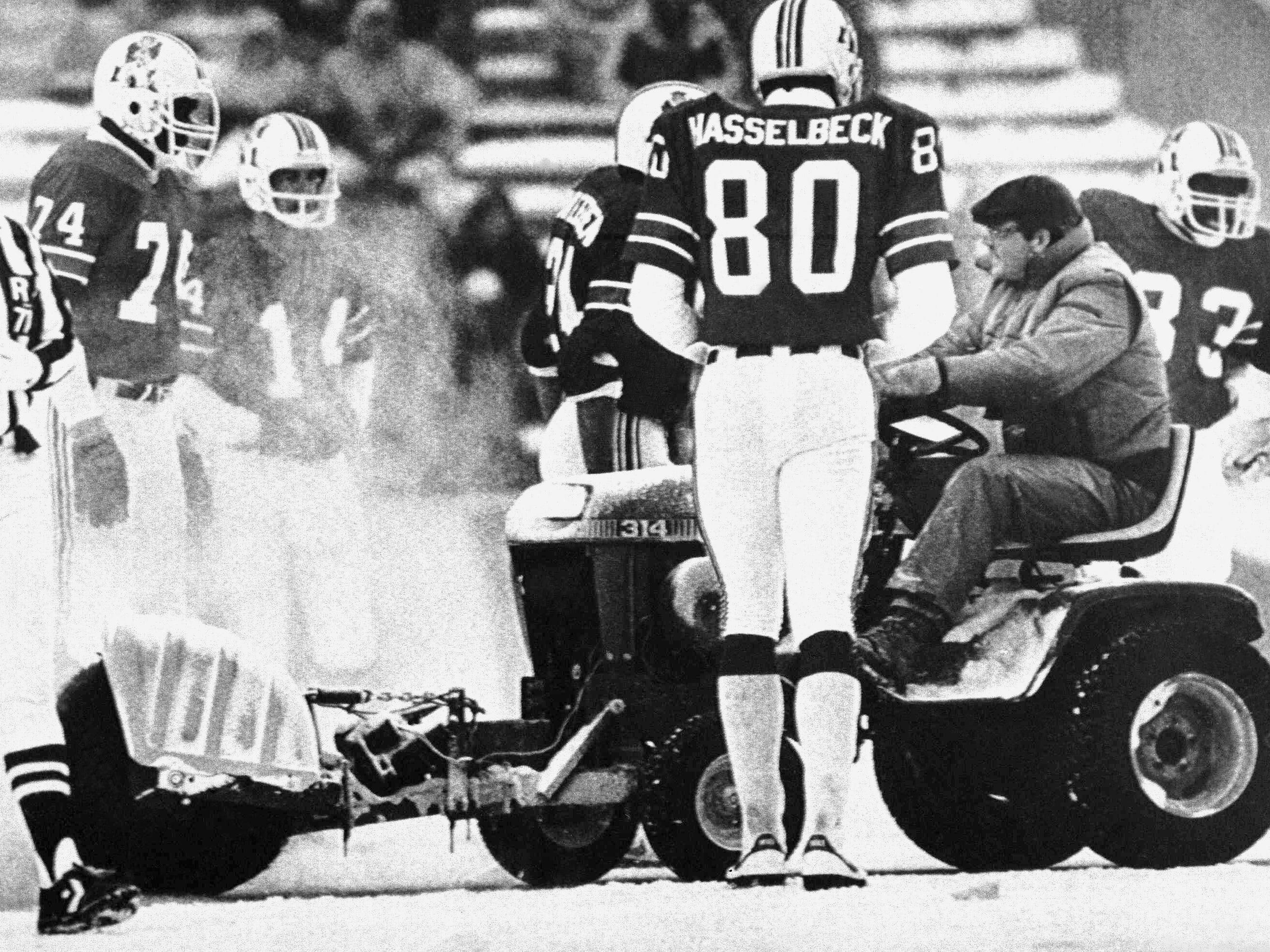 Dec. 12, 1982: A worker at Schaefer Stadium in Foxboro drives a tractor  to clear the snow away while members of the New England Patriots watch during a game against the Miami Dolphins. The Patriots won the game, 3-0.