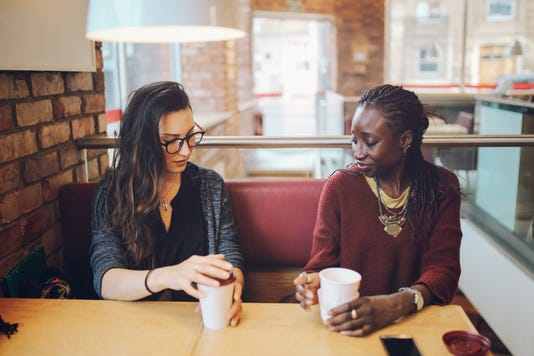 Young Women Sitting And Talking At The Coffee Break
