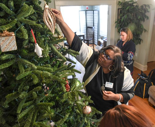Stacie Cowan, the new Anderson Interfaith Ministries director of Women and Children Succeeding, helps decorate a Christmas tree with Martha Everette at the home in Anderson in December.