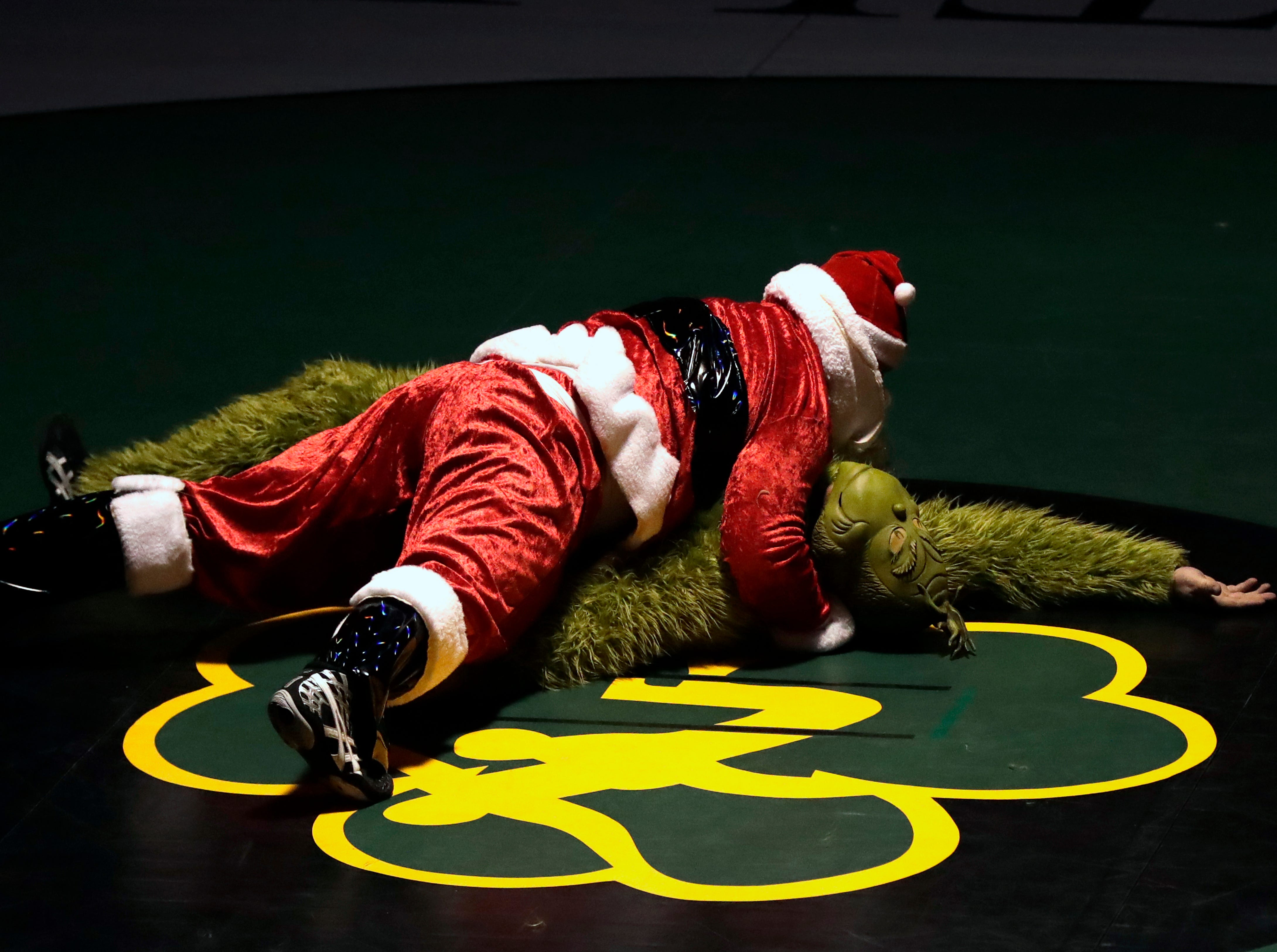 Santa pins The Grinch prior to Freedom High School against Waupaca High School during their wrestling meet Thursday, December 6, 2018, in Freedom, Wis. 
