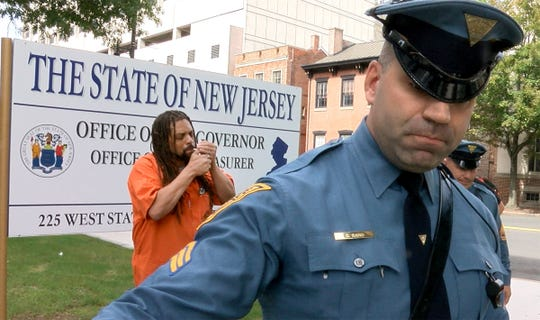 State Police moves a photographer away as Ed Forchion, known best as NJ Weedman, lights up a marijuana cigarette outside the Governor's office on West State Street in Trenton Thursday, September 27, 2018.  He billed this as his boldest stunt - selling marijuana outside the Statehouse while daring police to arrest him.