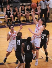 Cooper's Deven Bailey, right, drives in the lane against the Abilene High defense. Cooper beat the Eagles 69-65 at the Catclaw Classic on Friday at Wylie's Bulldog Gym.