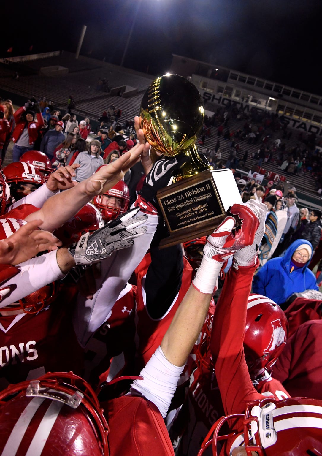 The Albany High School Lions hoist the championship trophy after Thursday's Class 2A Division II quarterfinal game at Shotwell Stadium Dec. 6, 2018. Final score was 41-28, Albany.