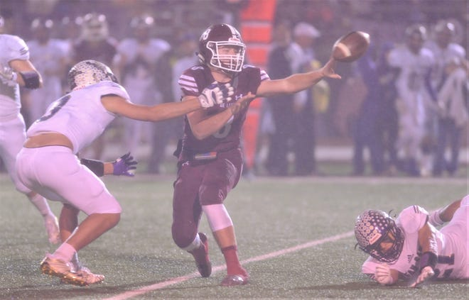 De Leon quarterback Kevin Yeager, center, pitches the ball to a teammate while a San Saba defender closes in. The ball ended up being fumbled and set a San Saba touchdown in the first quarter of the Class 2A Division I state quarterfinal playoff game Thursday at Gordon Wood Stadium in Brownwood.