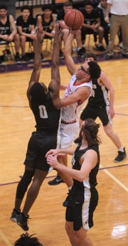 Cooper's Ben Thompson, center, drives between two Fort Worth Chisholm Trail defenders. Chisholm Trail beat the Cougars 64-62 in pool play at the Catclaw Classic.