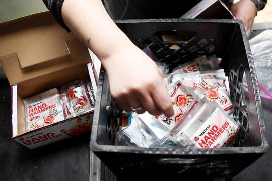 "Adrienne Sigmon organizes a box of hand warmers and emergency blankets before heading out into the community to help prepare the homeless for this weekend's winter weather. ""We're about taking care of people,"" said Sigmon of the organization, which began it's street medic team after a woman died of hypothermia while sleeping along the French Broad River in 2016."