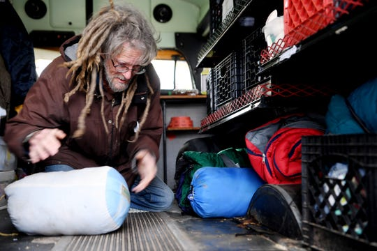 """BeLoved Asheville volunteer """"G-Rock,"""" stacks sleeping bags on the BeLoved Asheville bus before going into the community to help the homeless prepare for this weekend's weather December 7, 2018."""