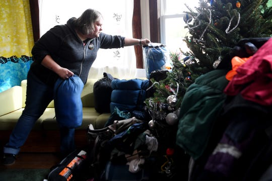 Adrienne Sigmon stacks sleeping bags at BeLoved Asheville December 7, 2018, as she and other volunteers of the organization prepare for this weekend's winter weather.