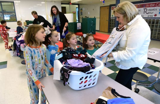 Avery Moore, Josarra Tyler, Holly McMahon and Tallis Sangasano help first grade teacher Mrs. Pat Nestleroade sort donated pajamas at Thomas Jefferson Elementary School in Binghamton.In a week, the school collected 120 pairs of new, warm winter pajamas for their fellow students. December 7, 2018.